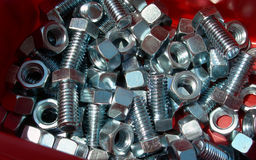 Nuts and bolts in red bin. Collection of shiny new nuts and bolts in red plastic bin Stock Image
