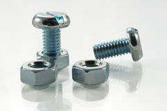 Nuts, bolts and reflections. Close up and low level angle on two metal bolts and two metal nuts arranged on a white reflective surface with white background royalty free stock photo