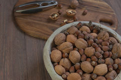 Nuts in the busket. Hazelnuts, walnuts and nutcracker on the wooden backgraund Royalty Free Stock Photography