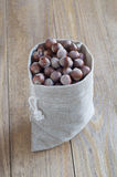 Nuts in a canvas pouch old desk. Hazelnuts in a canvas pouch old desk. CloseUp Royalty Free Stock Photography