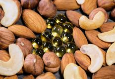 Nuts and capsules with vitamins. Closeup shot stock photo
