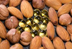 Nuts and capsules with vitamins. Closeup shot royalty free stock images
