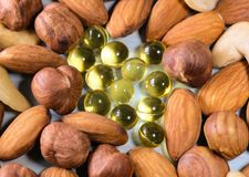 Nuts and capsules with vitamins. Closeup shot stock photography