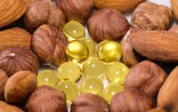 Nuts and capsules with vitamins. Closeup shot stock image