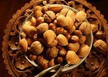 Nuts on carved wood table royalty free stock images