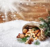 Nuts cascading onto winter snow Stock Photo