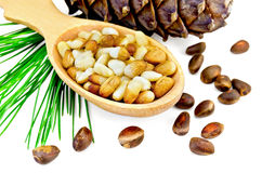 Nuts of cedar  in a wooden spoon and a bump Royalty Free Stock Image