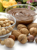 Nuts and chocolate on flower background Stock Photos