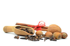 Nuts, cinnamon sticks and some cloves. On white Stock Images