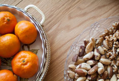 Nuts and citrus. Closeup photo of a glass plate full of nuts and a dish of citrus fruit stock photo