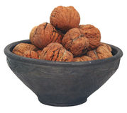 Nuts on the dish #2. Black clay ceramic dish full of walnuts isolated on white background Stock Photos