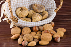 Nuts and dried figs. Little basket with dried figs and nuts, over wooden table Royalty Free Stock Photos