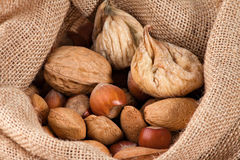 Nuts and dried figs. Closeup on a little sack with nuts and dried figs Royalty Free Stock Image