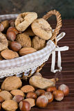 Nuts and dried figs. Little basket with dried figs and nuts, over wooden table Stock Images