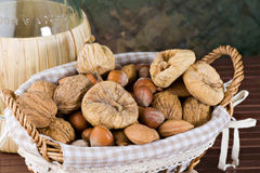 Nuts and dried figs. Little basket with dried figs and nuts, over wooden table Royalty Free Stock Image