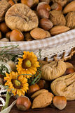 Nuts and dried figs. Little basket with dried figs and nuts, over wooden table Stock Photos