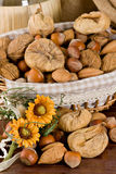 Nuts and dried figs. Little basket with dried figs and nuts, over wooden table Royalty Free Stock Photography