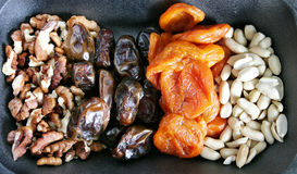 Nuts and dried fruits. On black background Stock Photography