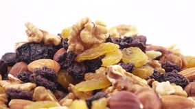 Nuts and dried fruits in bulk. Weight of nutmixture in bulk on a white background stock video footage