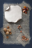 Nuts and dried fruits on a piece of burlap. Walnuts, hazelnuts and dates on a piece of burlap. A blank sheet of paper for inscription. Top view and copy space stock photo