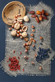 Nuts and dried fruits on a piece of burlap. Walnuts, hazelnuts, dates, raisins, goji berries on a piece of sacking. Top view stock image