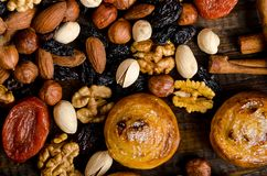 Nuts, dried fruits, pistachios and homemade cookies are scattered from the bag on the table stock photography