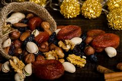 Nuts, dried fruits, pistachios and other scattered from the bag on the table. Horizontal frame stock photo