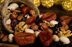 Nuts, dried fruits, pistachios and other scattered from the bag on the table. Horizontal frame royalty free stock photography