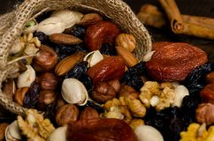 Nuts, dried fruits, pistachios and other scattered from the bag on the table. Horizontal frame royalty free stock images