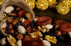 Nuts, dried fruits, pistachios and other scattered from the bag on the table royalty free stock photography