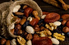 Nuts, dried fruits, pistachios and other scattered from the bag on the table royalty free stock photo