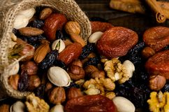 Nuts, dried fruits, pistachios and other scattered from the bag on the table. Horizontal frame royalty free stock photos