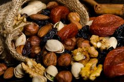 Nuts, dried fruits, pistachios and other scattered from the bag on the table. Horizontal frame stock images