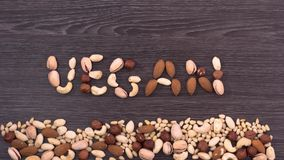 Nuts fall and form a word VEGAN on the dark wooden background. Stop motion stock video footage