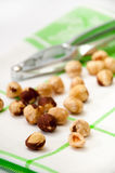 Nuts in focus with metal nutcracker in the background Stock Photography