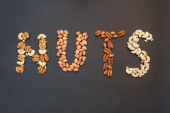 Nuts in the form of inscriptions `Nuts`. The word `Nuts` laid out with nuts on a black background royalty free stock photos