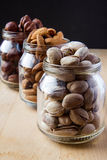 Nuts in glass jars. On wooden table Stock Image