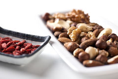 Nuts and Goji Berries. On plates Stock Photos