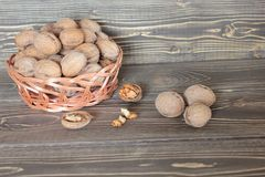 Nuts greckie in a braiding basket lie on a wooden table. Nuts greckie in a braiding basket and the chopped nuts lie on a wooden table Royalty Free Stock Photo