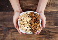 Nuts in hands. Different kinds of nuts in a plate in hands on the wooden table stock photos