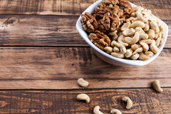 Nuts in hands. Different kinds of nuts in a plate in hands on the wooden table stock image