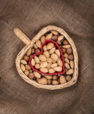 Nuts in heart shaped basket and bowl Royalty Free Stock Image