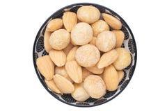 nuts Hintergrund Nahaufnahme von gebratenen und gesalzenen Macadamia und von Mandelnüssen in der keramischen Schüssel lokalisiert lizenzfreies stockfoto