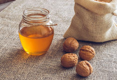 Nuts with honey. Walnuts in a canvas bag and honey in a jar. Wooden table with linen napkin. The sweet honey Royalty Free Stock Photos