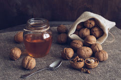 Nuts with honey. Walnuts in a canvas bag and honey in a jar. Wooden table with linen napkin. The sweet honey Royalty Free Stock Photo