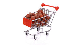 Nuts in miniature shopping cart isolated Royalty Free Stock Photos