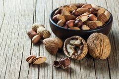Nuts mix dried fruits in bowl, different kind of nut. Nuts mix dried fruits, different kind of nut, healthy food on wooden table. Walnut, hazelnut, pistachio royalty free stock photography