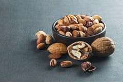Nuts mix dried fruits in bowl, different kind of nut. Nuts mix dried fruits, different kind of nut, healthy food on wooden table. Walnut, hazelnut, pistachio stock photography
