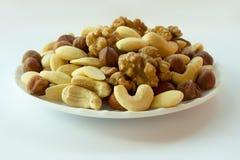 Nuts mixture hazelnuts almonds walnuts cashew. Nuts mixture - hazelnuts almonds walnuts cashew on a plate on a white background Royalty Free Stock Photo