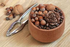 Nuts and nutcracker. Wood cup with nuts and nutcracker Royalty Free Stock Photography